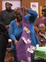 Sister Elder breaks out a money-ladened gift